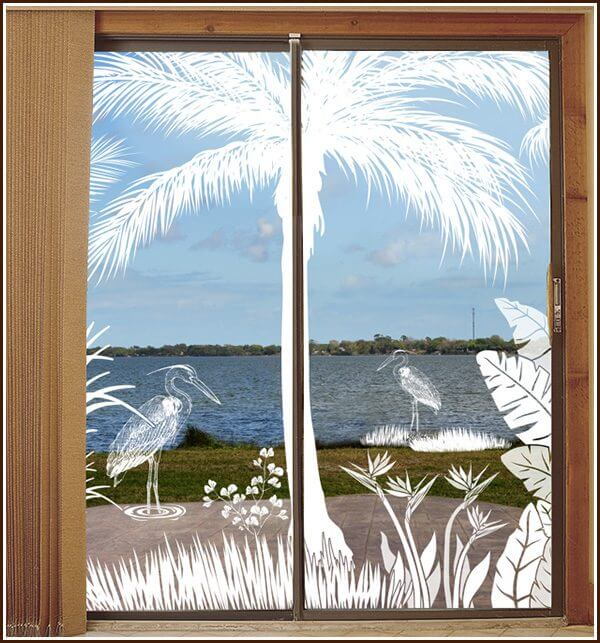 A river view is enhanced with the etched glass window film design, Heron Hideaway.
